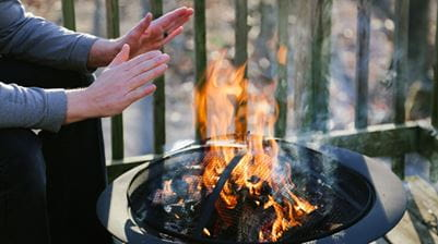 Hands warning up by fire pit.